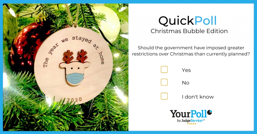 a christmas bauble of a reindeer wearing a facemask hanging on a chirtmas tree